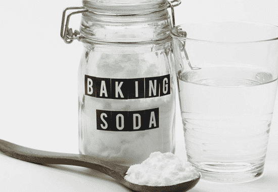 Baking soda in a jar and spoon with a glass of water